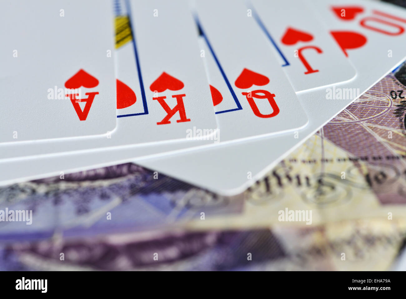 Gambling with money playing cards - Stock Image