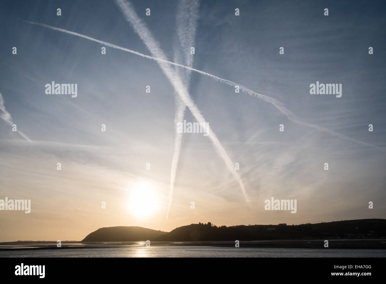 Ferryside, UK. 10th March, 2015. Airplane vapour vapor trails across the sky from Ferryside village at sunset. Llanstephan - Stock Image