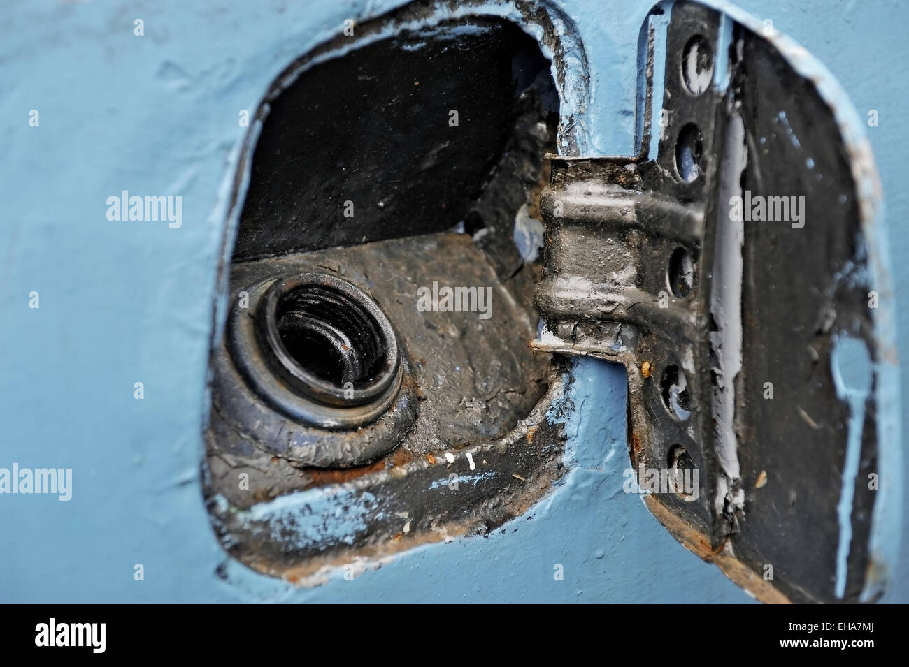 Detail with a fuel cap from a junk abandoned blue car - Stock Image
