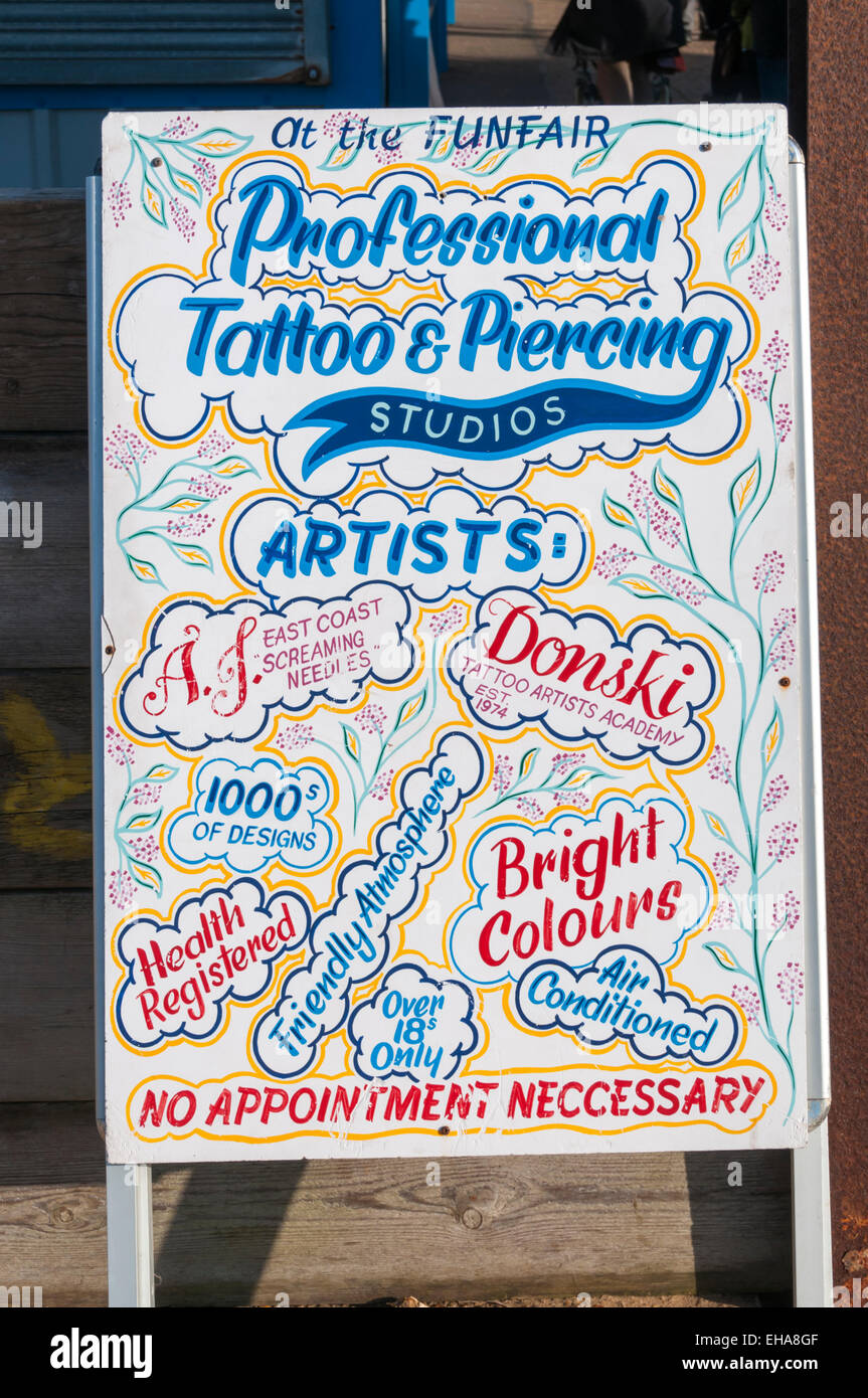 Sign for a tattoo parlour at Hunstanton Funfair. - Stock Image