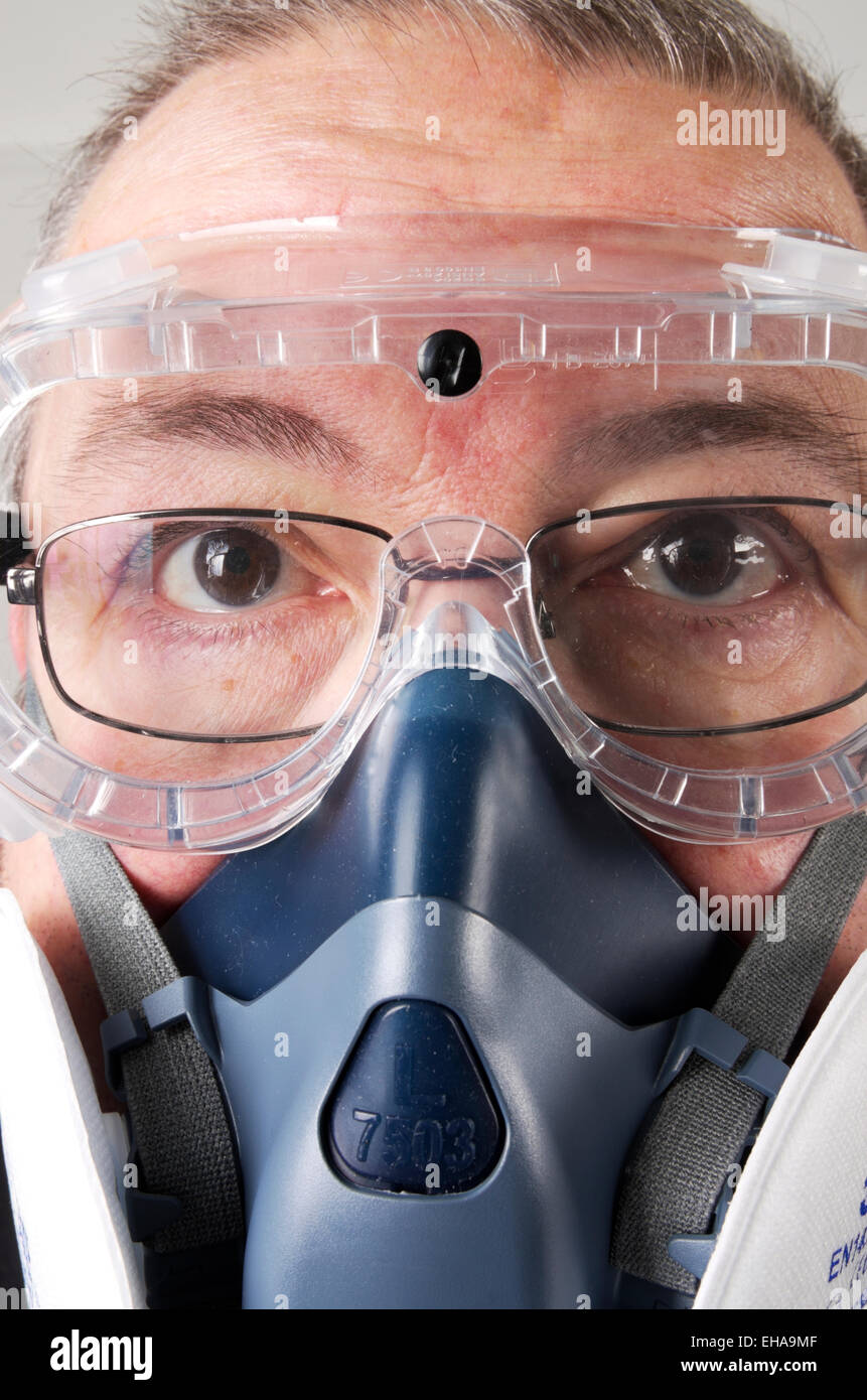 Staring Man in Spectacles Wearing Respirator and Safety Goggles - Stock Image