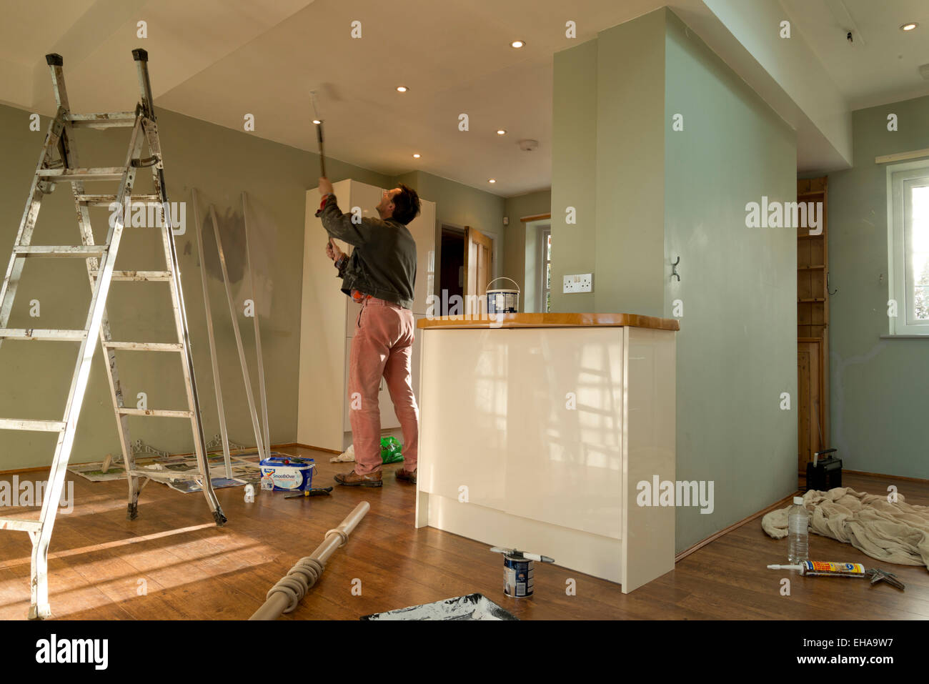 Man using a paint roller on the ceiling. Decorating the kitchen of a house. - Stock Image
