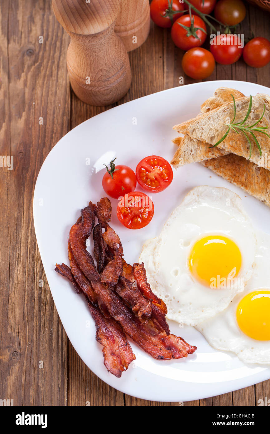 Fried egg and bacon on a plate with spices and vegetables. Studio shot - Stock Image