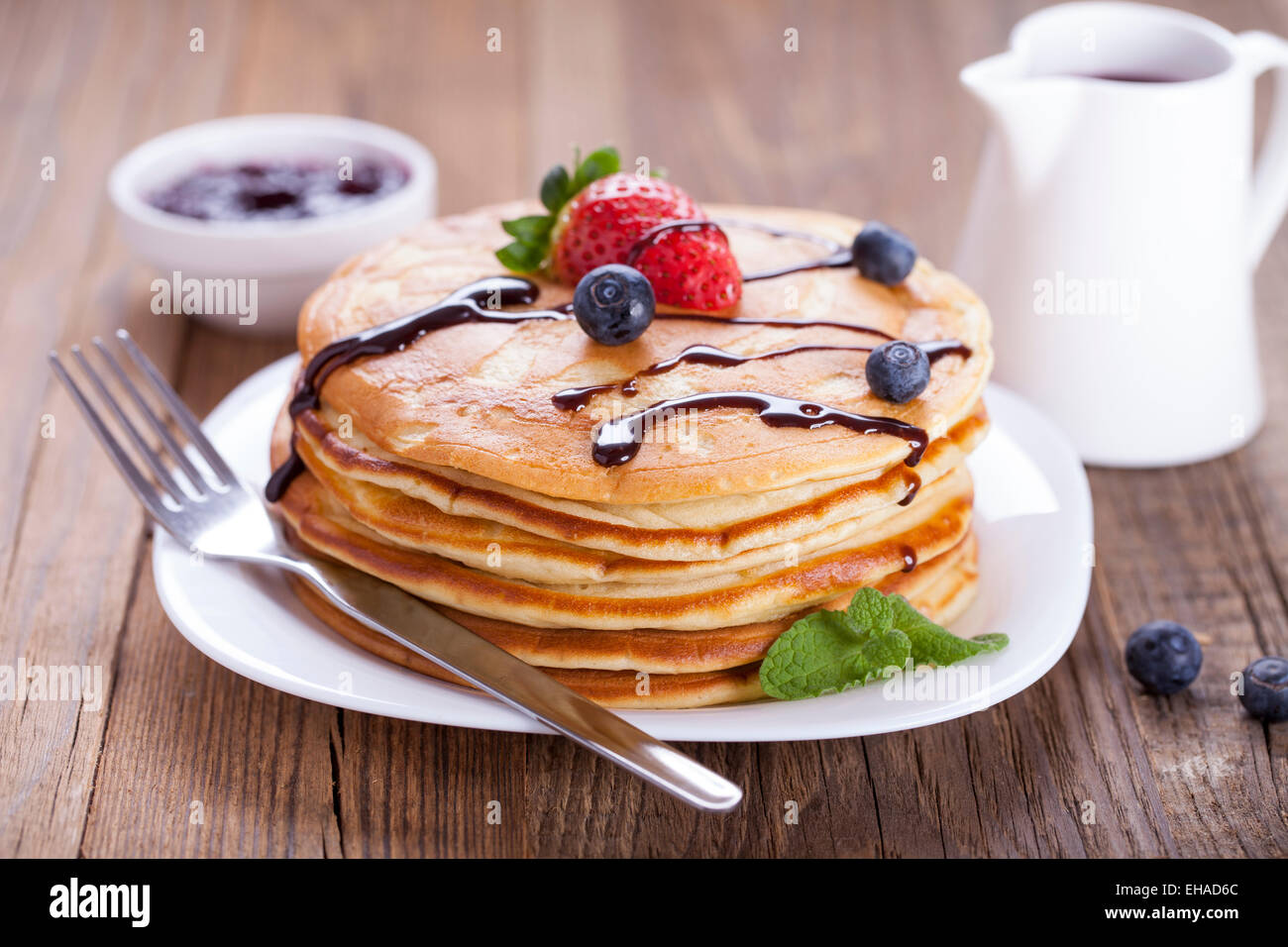 Delicious sweet American pancakes on a plate with fresh fruits and addons. - Stock Image