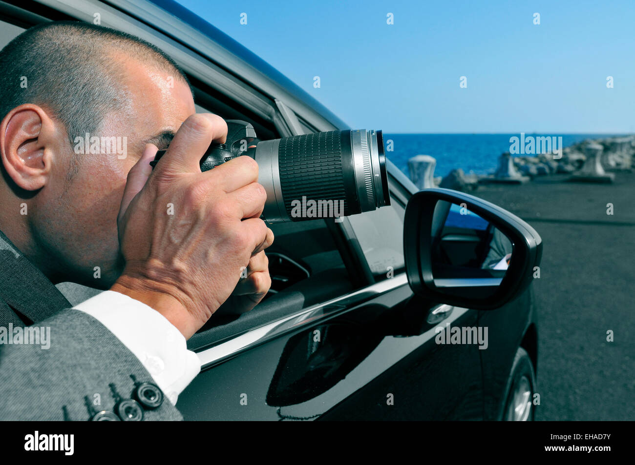 a detective or a paparazzi taking photos from inside a car - Stock Image
