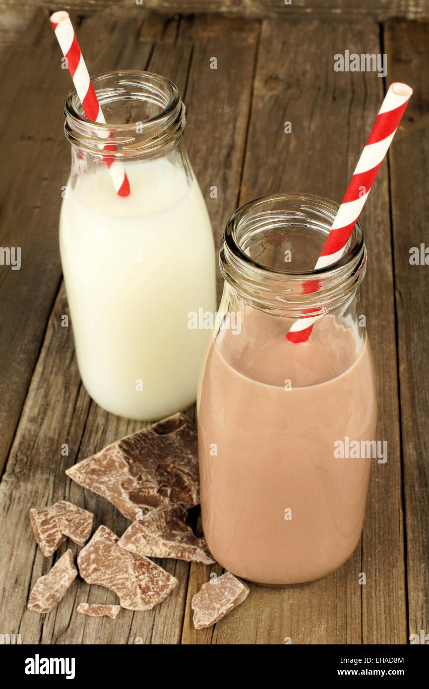 Chocolate and regular milk in traditional bottles with straws on old wood background - Stock Image