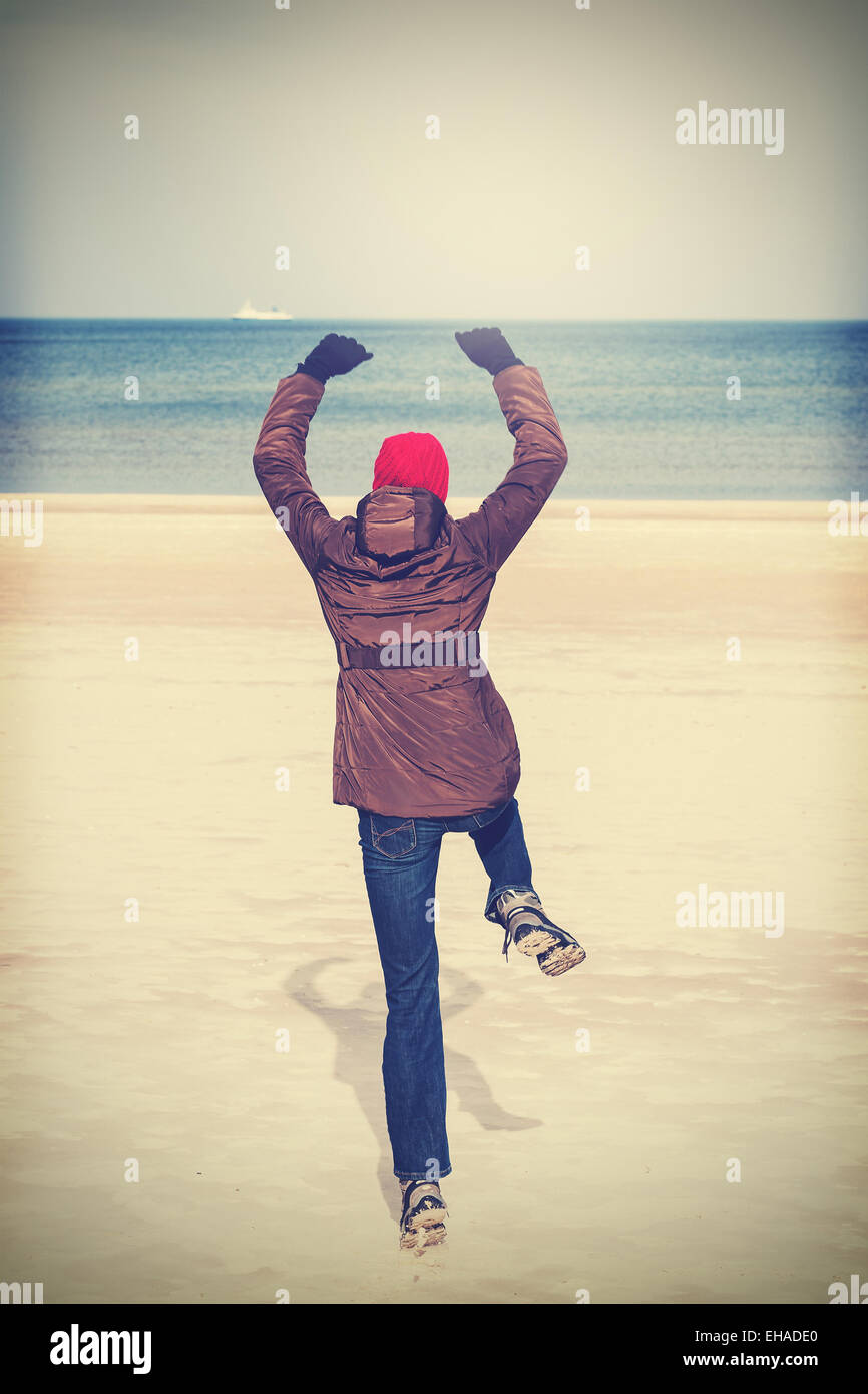 Retro filtered photo of woman jumping on beach, winter active lifestyle concept. - Stock Image