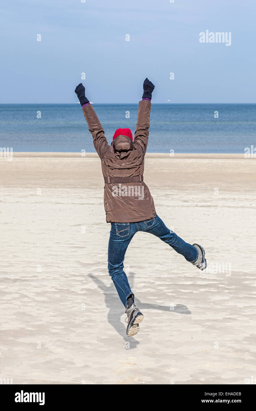 Woman jumping on beach, winter active lifestyle concept. - Stock Image