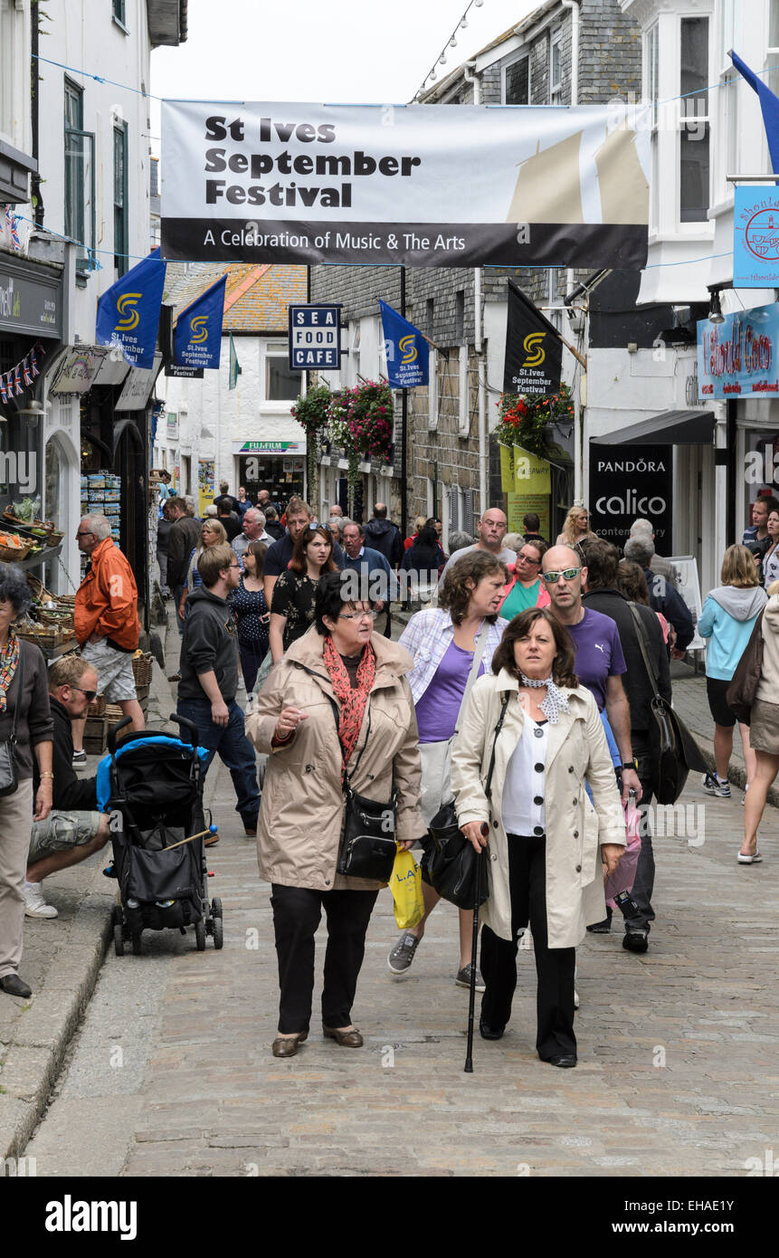 Tourists walking in Fore Street, St Ives, Cornwall. This is the main shopping street in this popular Cornish seaside - Stock Image