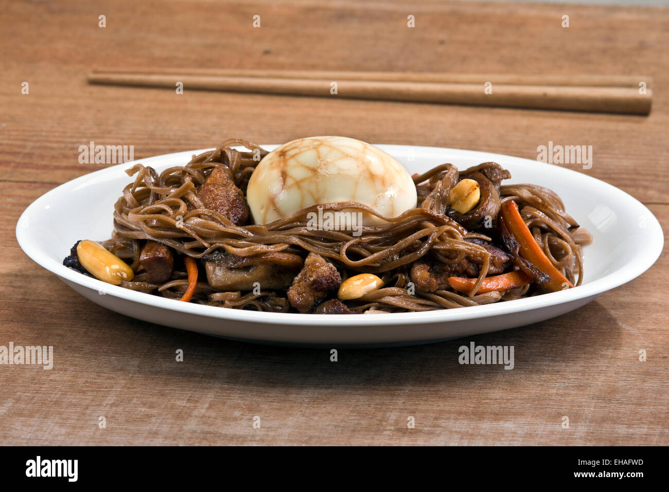 Traditional Chinese tea egg served on a nest of stir fried soba noodles with pork, oyster mushroom and peanuts. - Stock Image