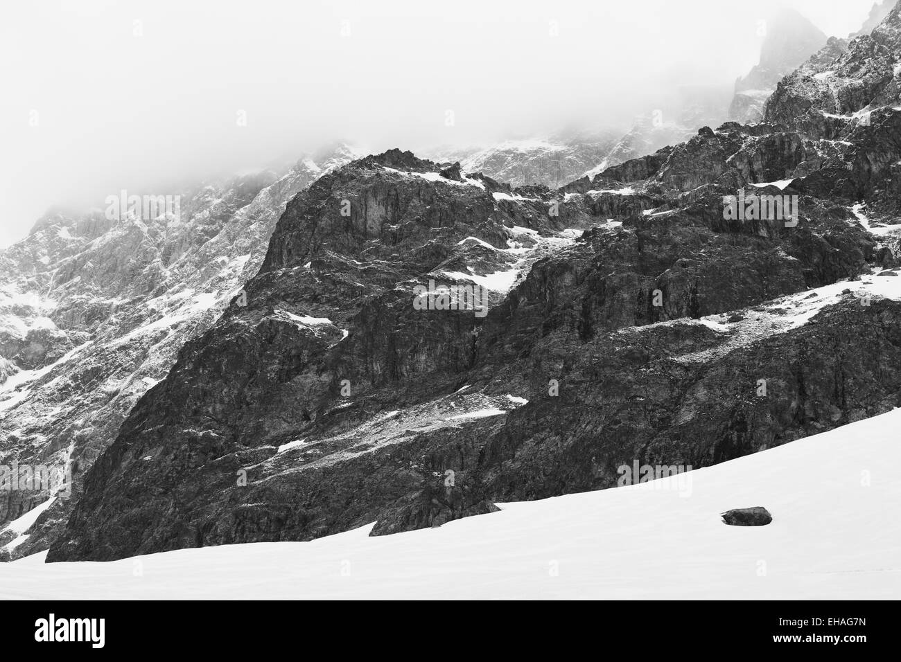 Rocky spur dusted with snow on the southern face of the Barre des Ecrins mountain, French Alps. - Stock Image
