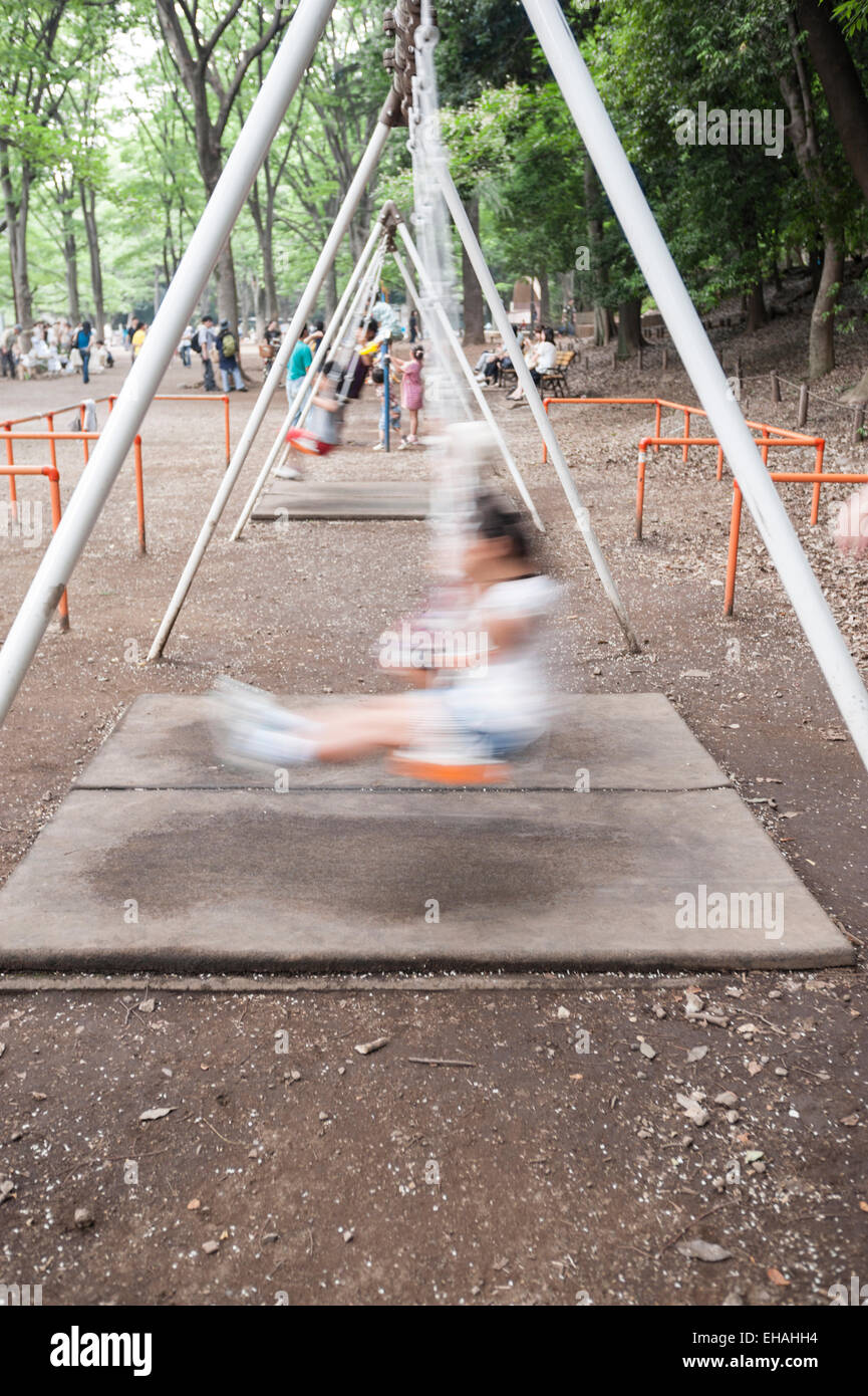 Motion Blurred Image Of A Young Girl Playing On A Swing Set In Stock
