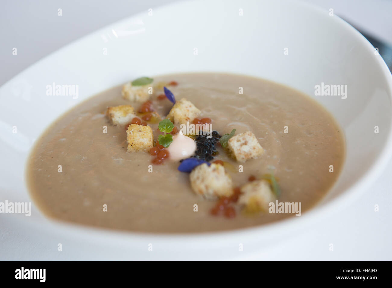 Caramelized cauliflower soup with smoked salmon mousse, Ossetra and tomato caviar. - Stock Image