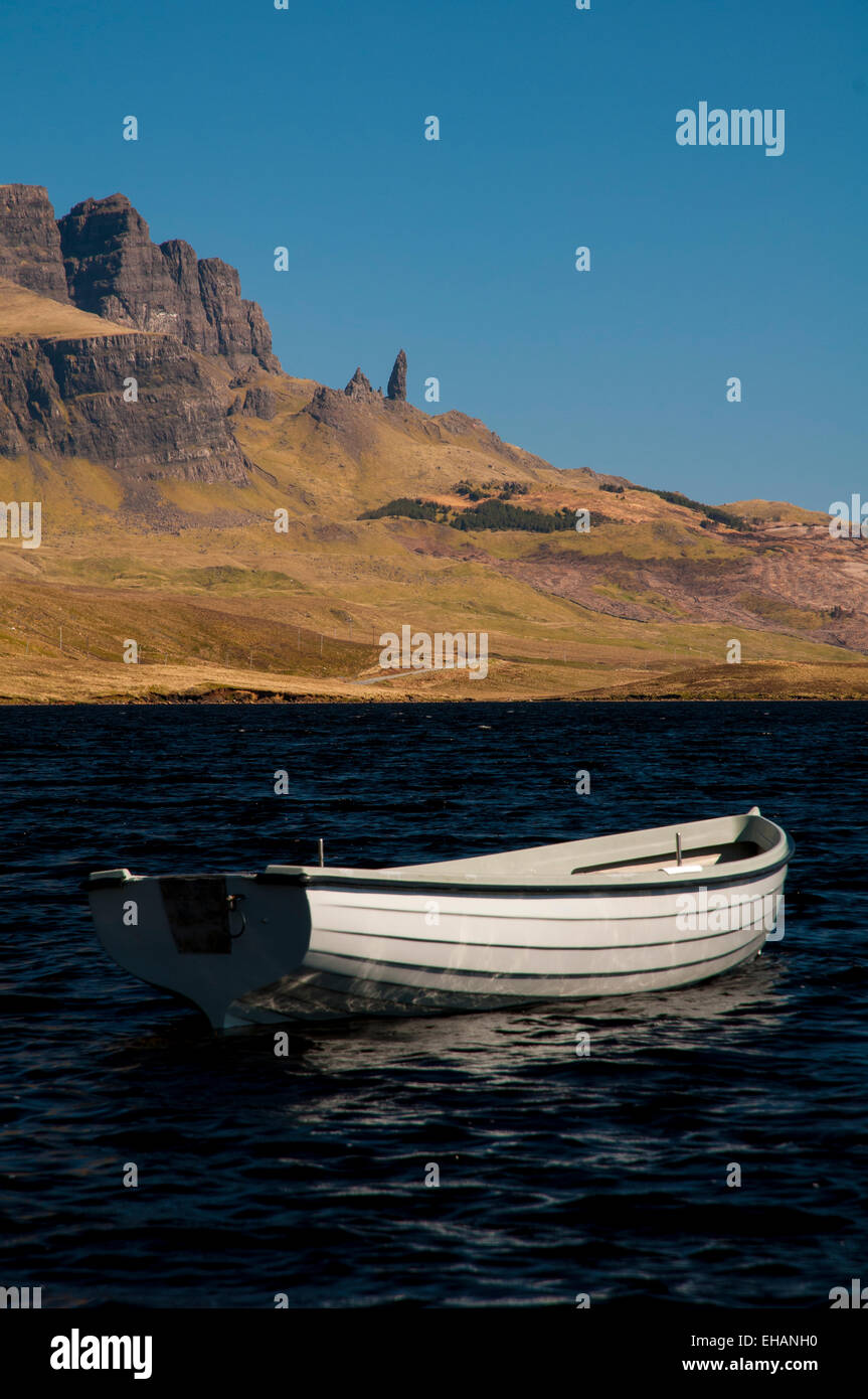 The Storr and the Old Man of Storr under a deep blue sky with a small white rowing boat on Loch Fada in the foreground. - Stock Image
