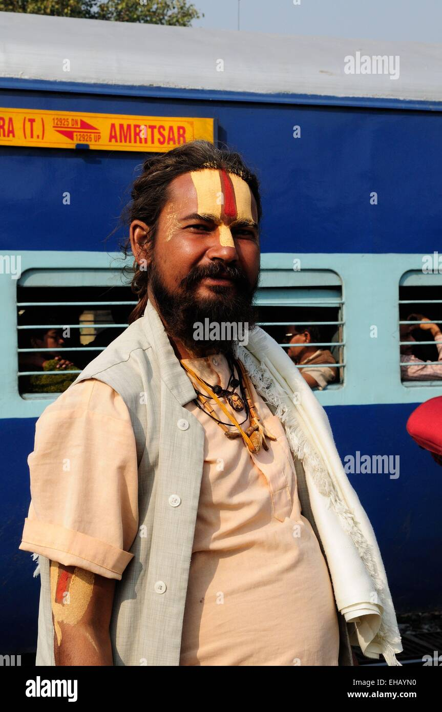 A Vishnu devotee  Sadhu Indian Holy man standing on the platform of Delhi Railway Station with a train in the background - Stock Image