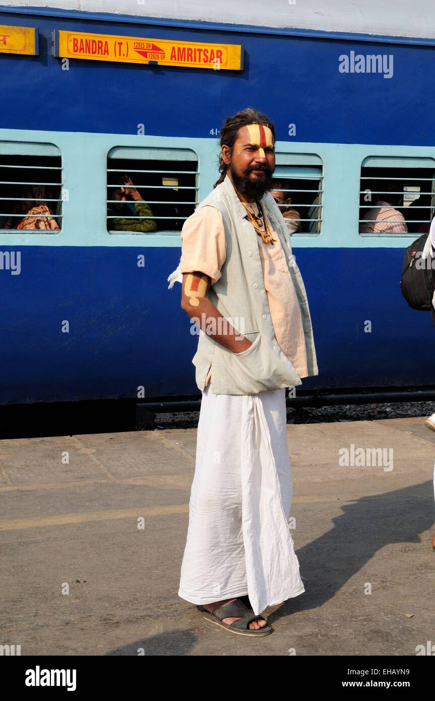 A Vishnu devotee  Sadhu Indian Holy man standing on the platform of Delhi Railway Station with a train in the background Stock Photo