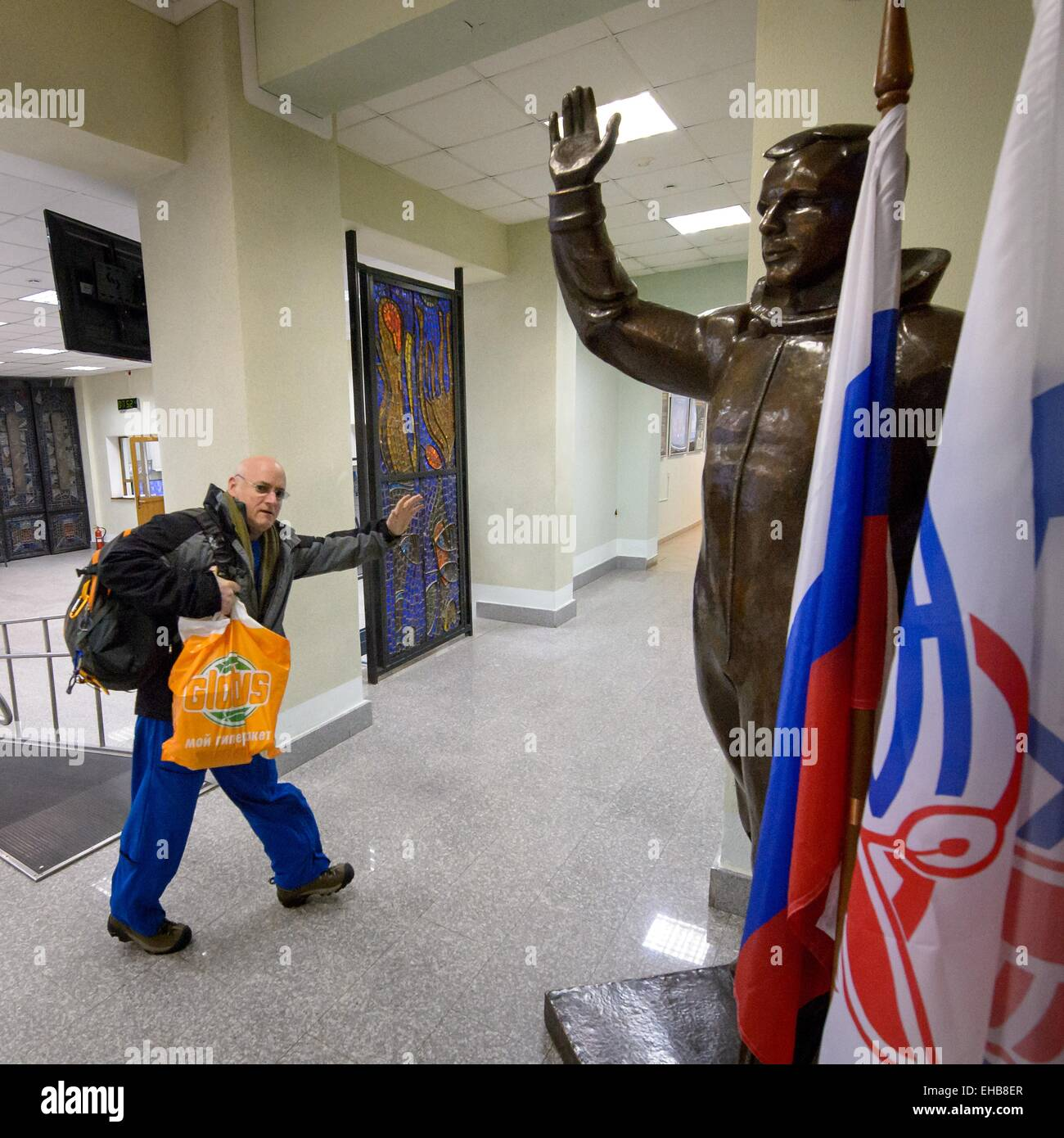 International Space Station Expedition 43 NASA Astronaut Scott Kelly waves hello as he passes a statue of Russian - Stock Image