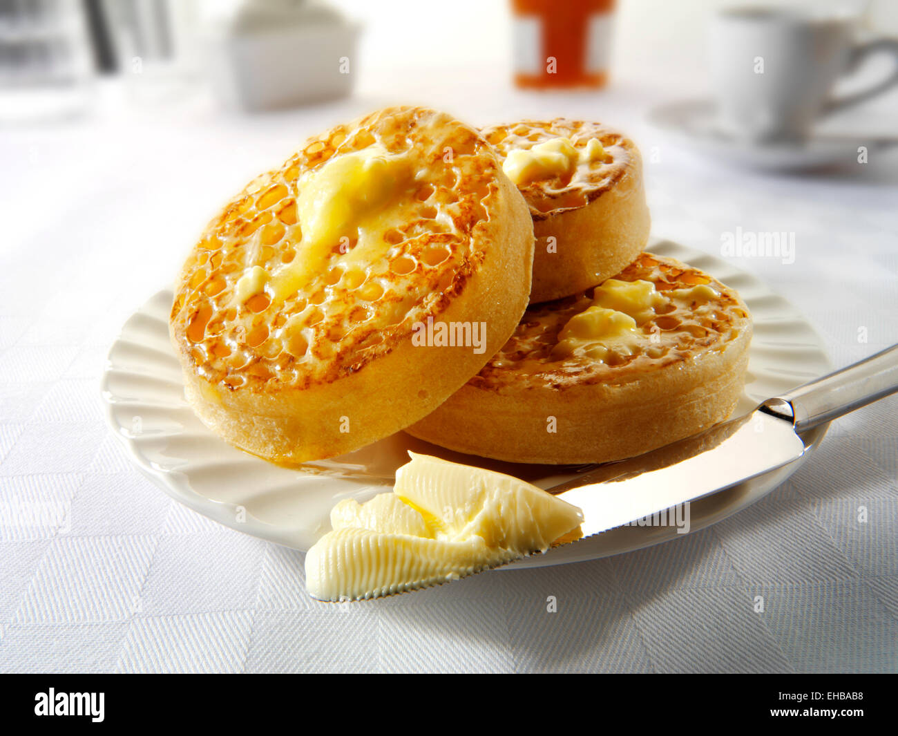 Traditional hot buttered toasted crumpets on a white plate on a table setting, with melted butter ready to eat - Stock Image