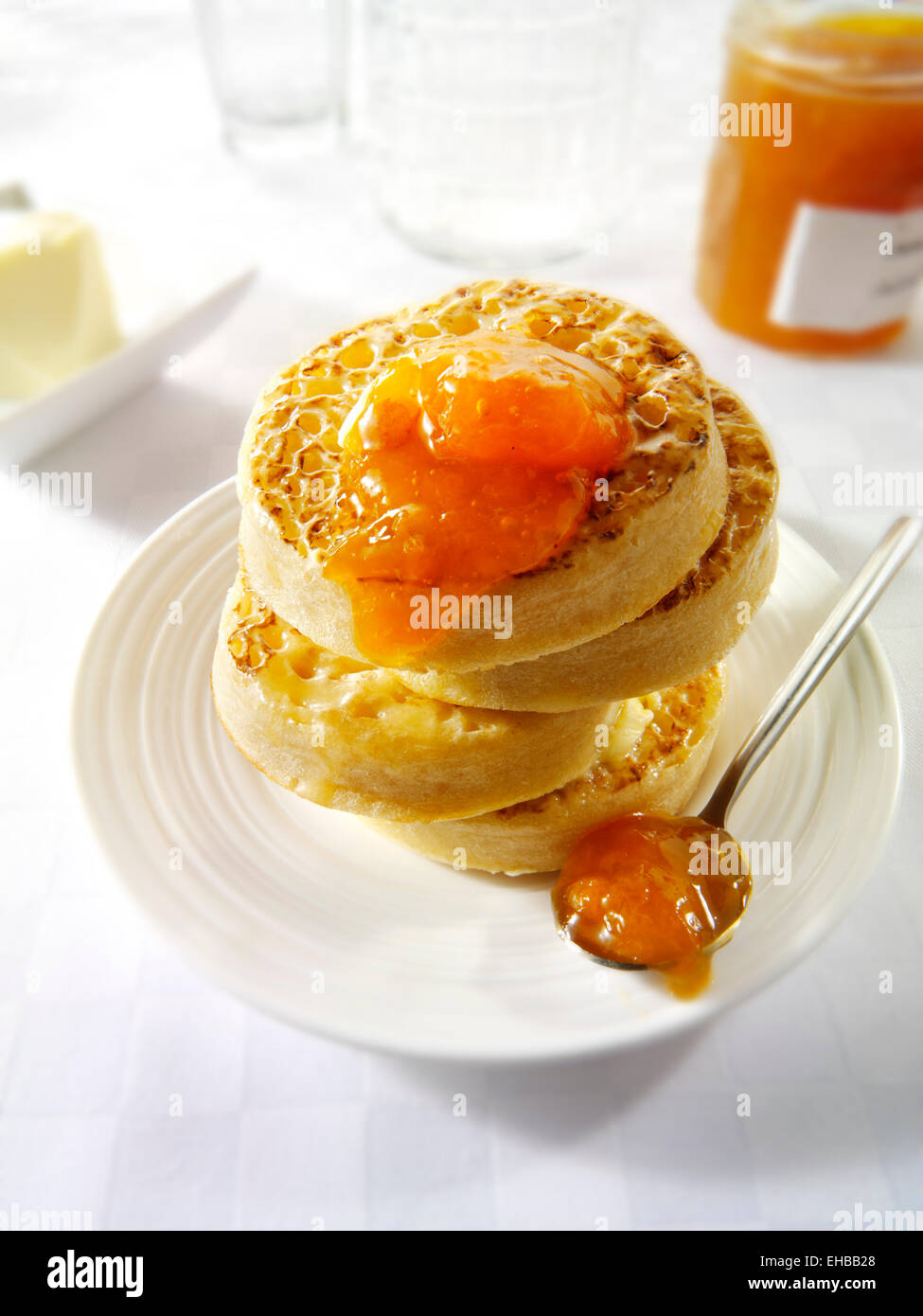 Close up of buttered toasted crumpets with apricot jam ready to eat in a white table setting - Stock Image