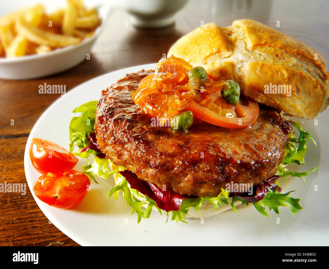 Beef burger with in a bun with salad, fries and relish - Stock Image