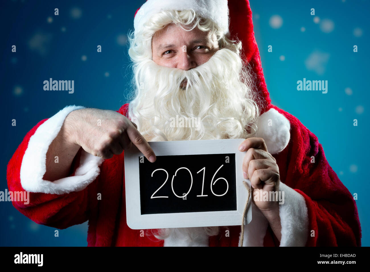Santa Claus pointing a finger on a blank slate with text 2016 Stock Photo