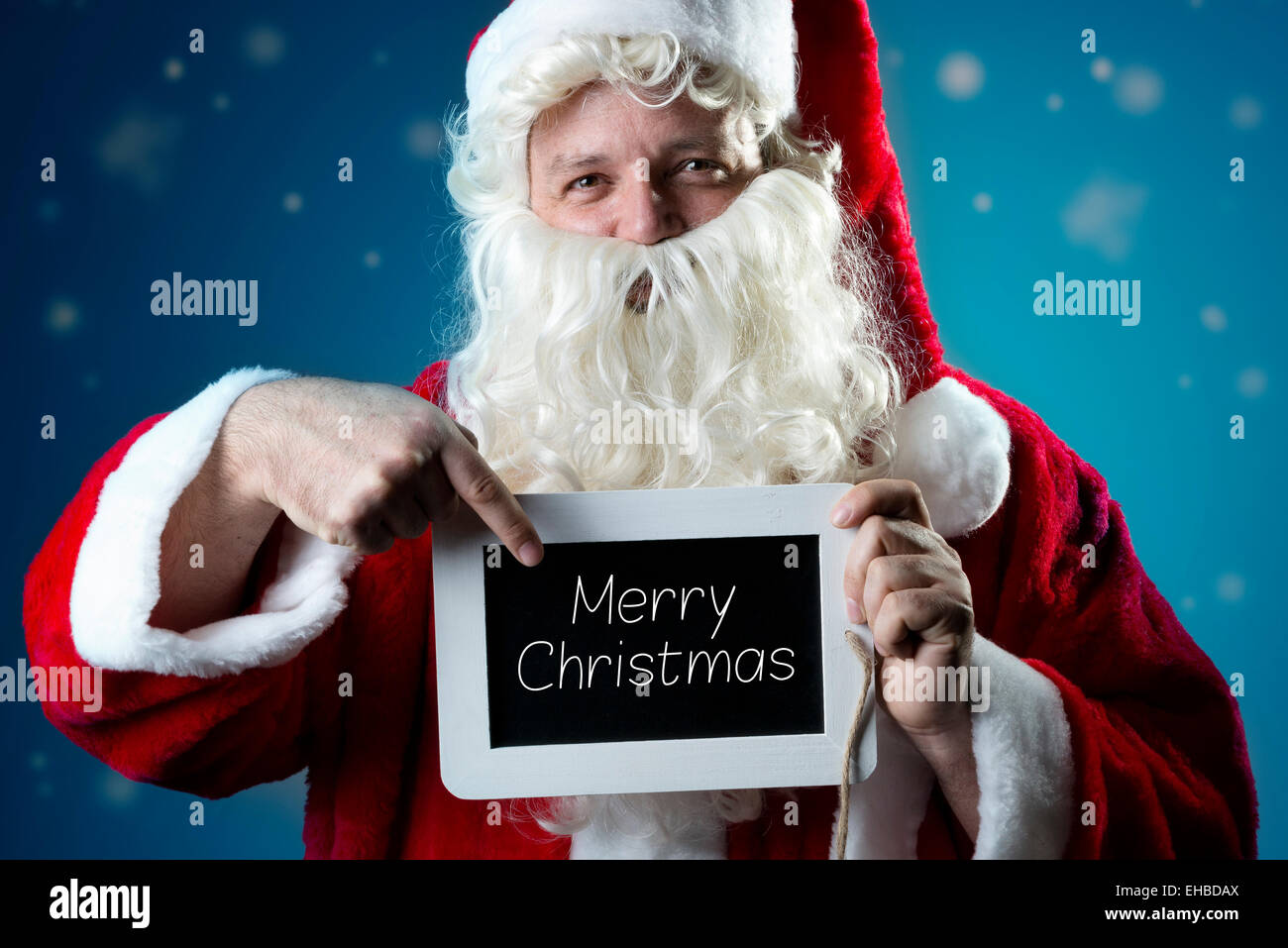 Santa Claus pointing a finger on a blank slate with text Merry Christmas Stock Photo