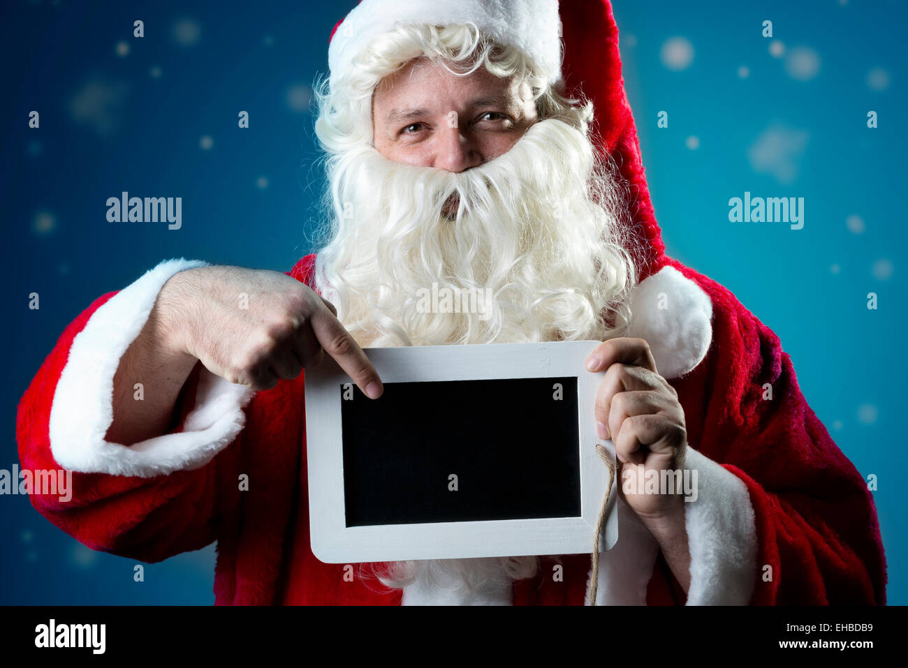 Image portrait of Santa Claus in red coat with snow pointing a finger on a blank slate Stock Photo