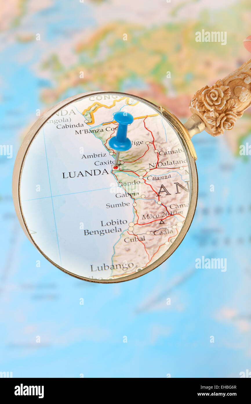 Blue tack on map of Africa with magnifying glass looking in on Luanda, Angola Stock Photo