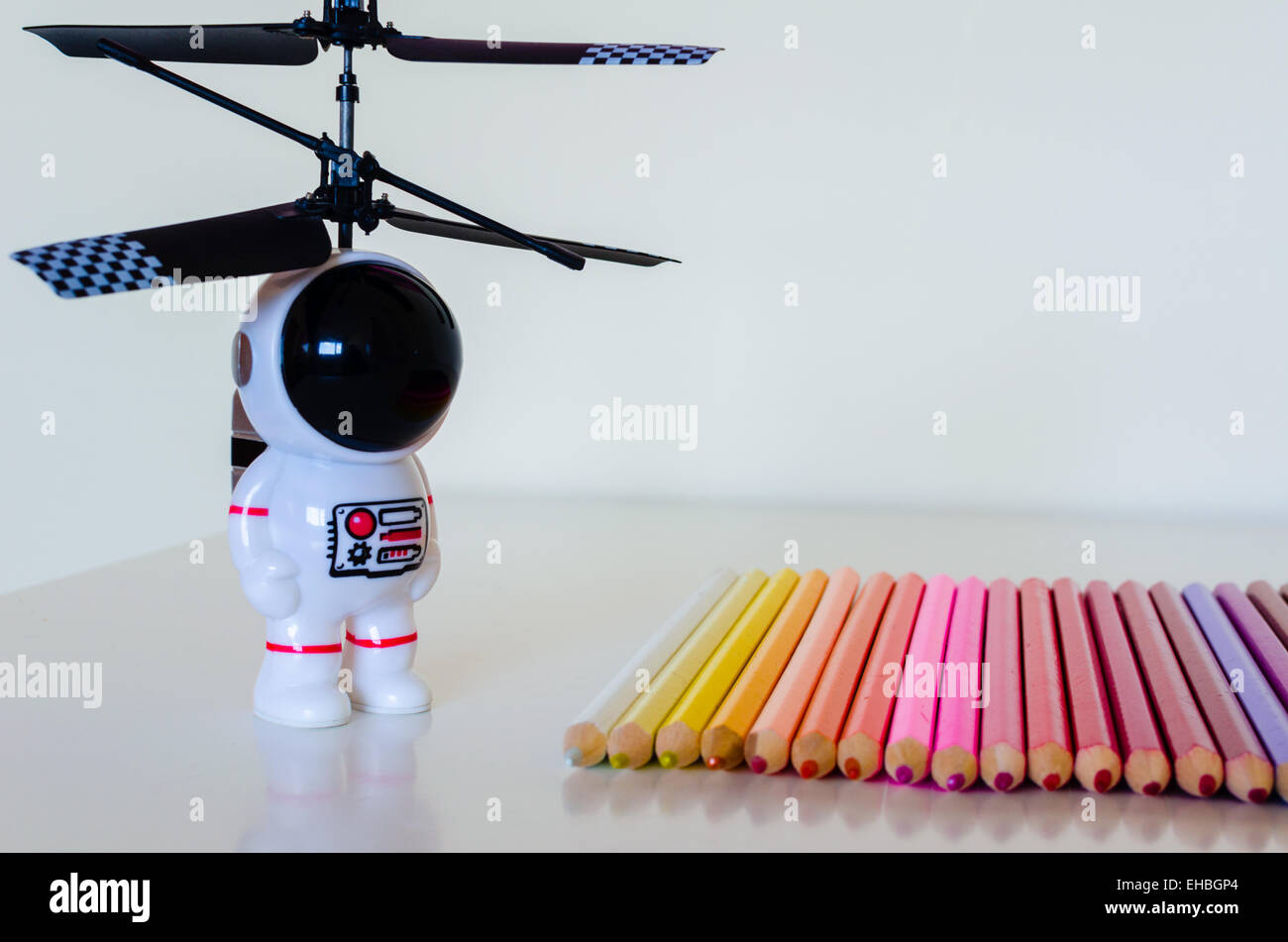 A child's toy spaceman looks towards a set of coloring crayons laid in a row on a white surface. There is some reflected detail. Stock Photo