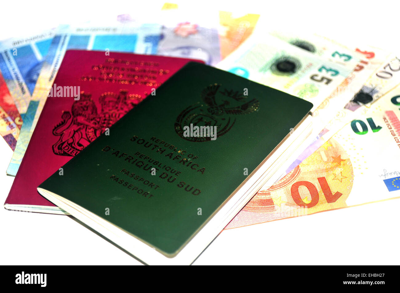 British and South African passports full of money photographed in a studio against a white background. Stock Photo