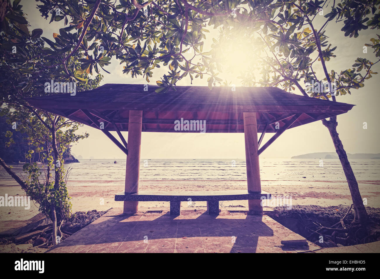 Retro filtered photo of a seaside bench at sunset. - Stock Image