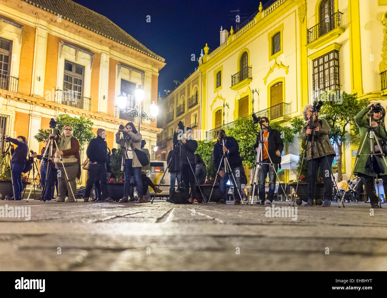 Seville Spain, group of photographers with tripods at night on guided photo tour aiming at the Giralda Cathedral - Stock Image