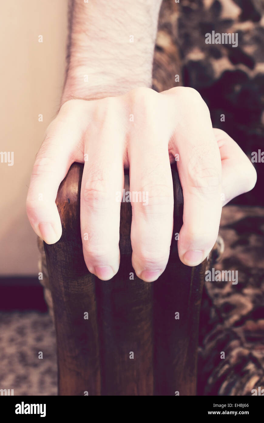 Male hand grabbing armchair - Stock Image