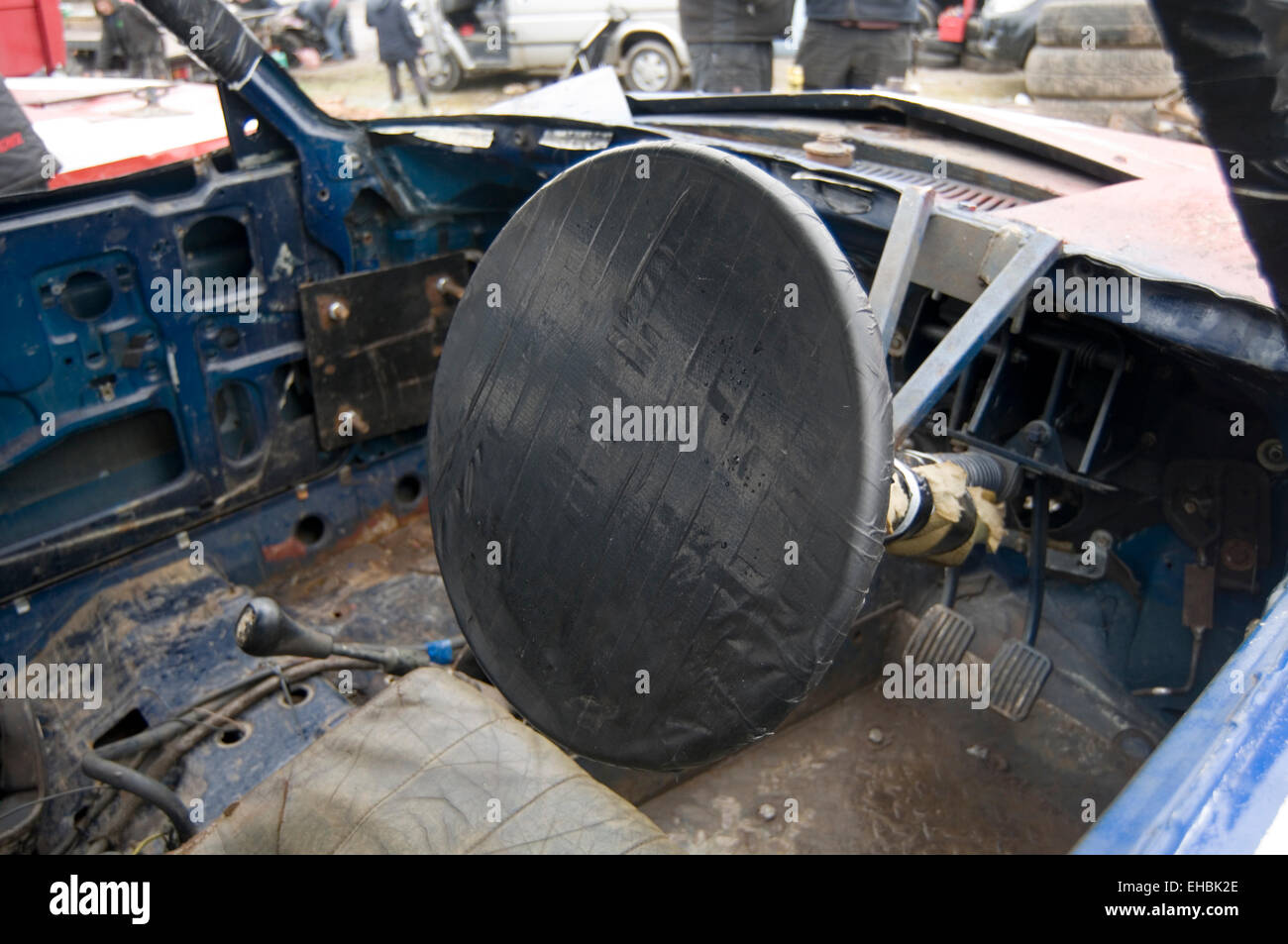 taped over steering wheel in demo derby car done so the driver doesn't break his hand when the wheel spins around - Stock Image
