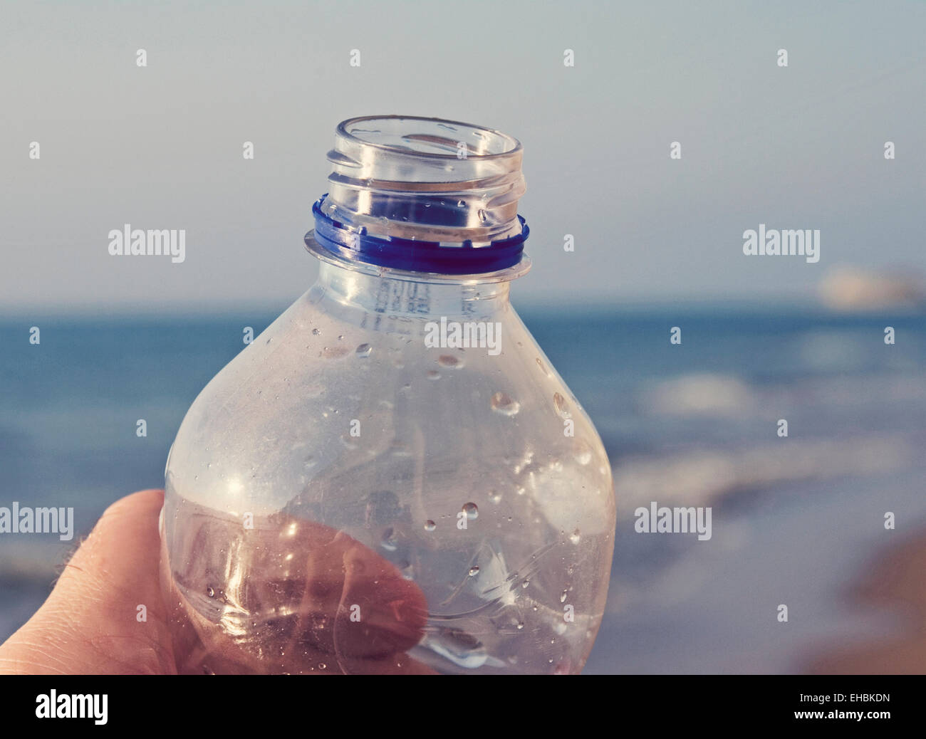 holding water bottle by the seashore - Stock Image