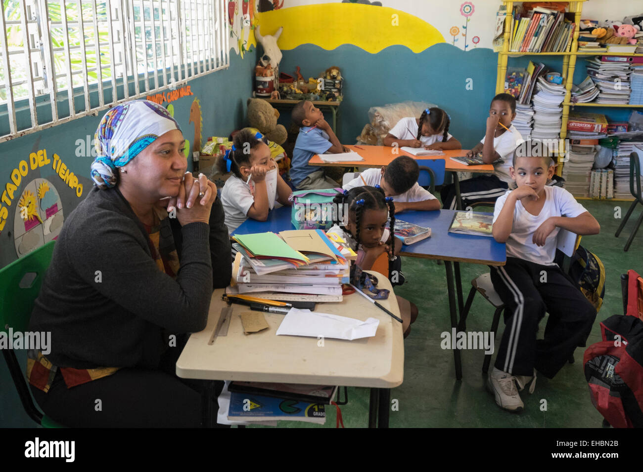 Primary school teacher with children studying in classroom of a village school near Puerto Plata, Dominican Republic, - Stock Image