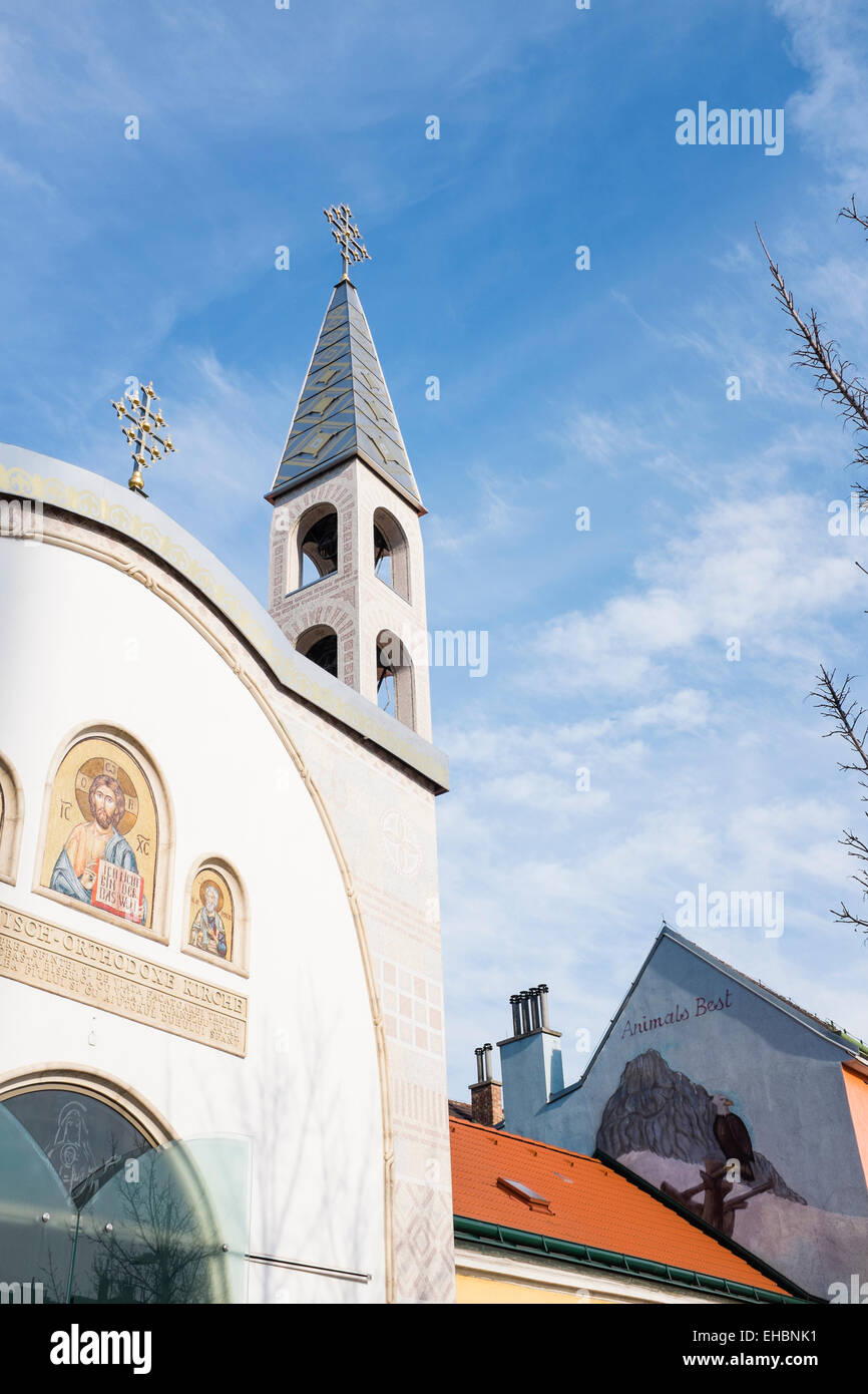 Simmering, Vienna. Orthodox church and pet shop in a sunny March day - Stock Image