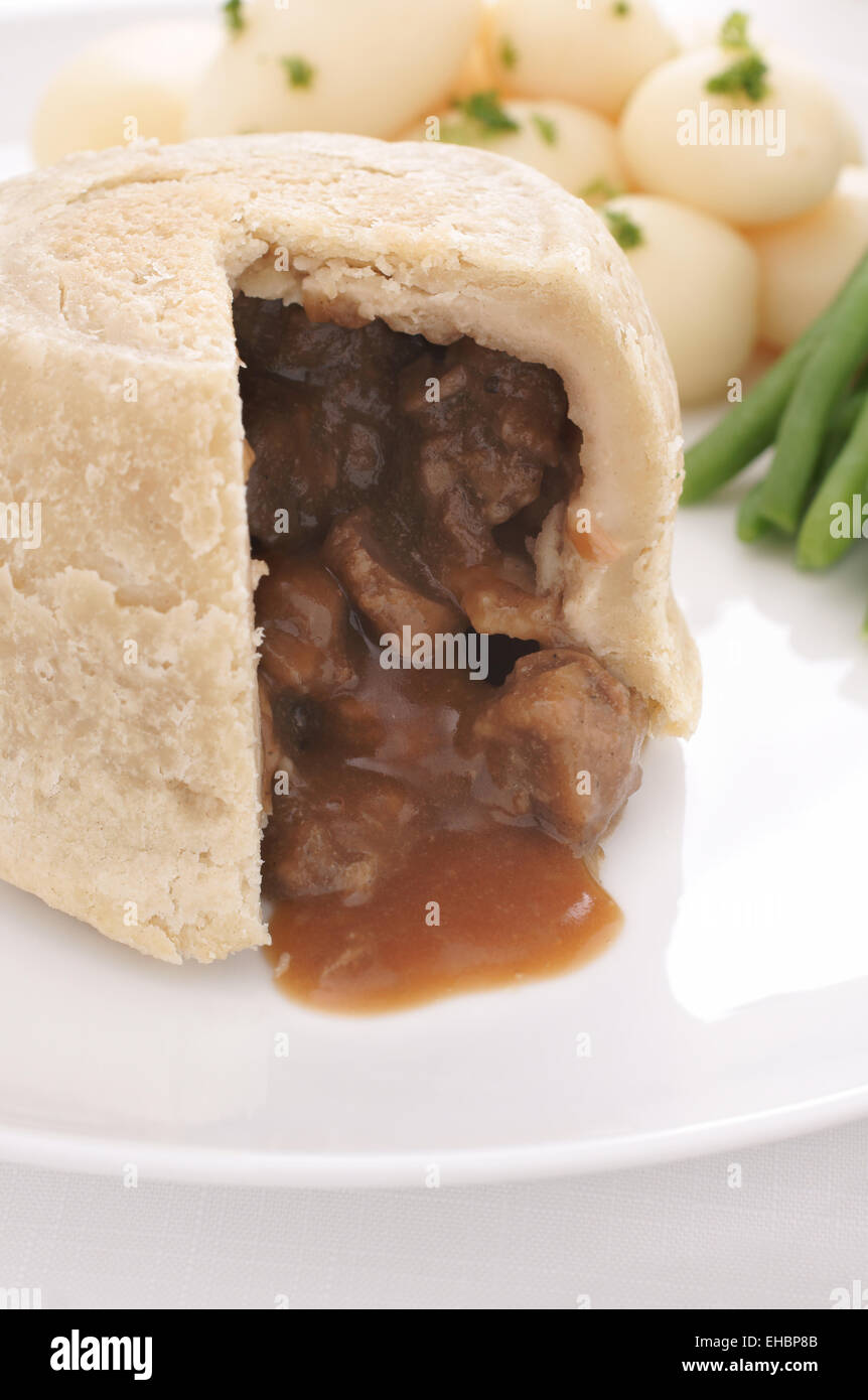 Steak and kidney pudding a traditional steamed suet pastry pie served with new potatoes and green beans - Stock Image