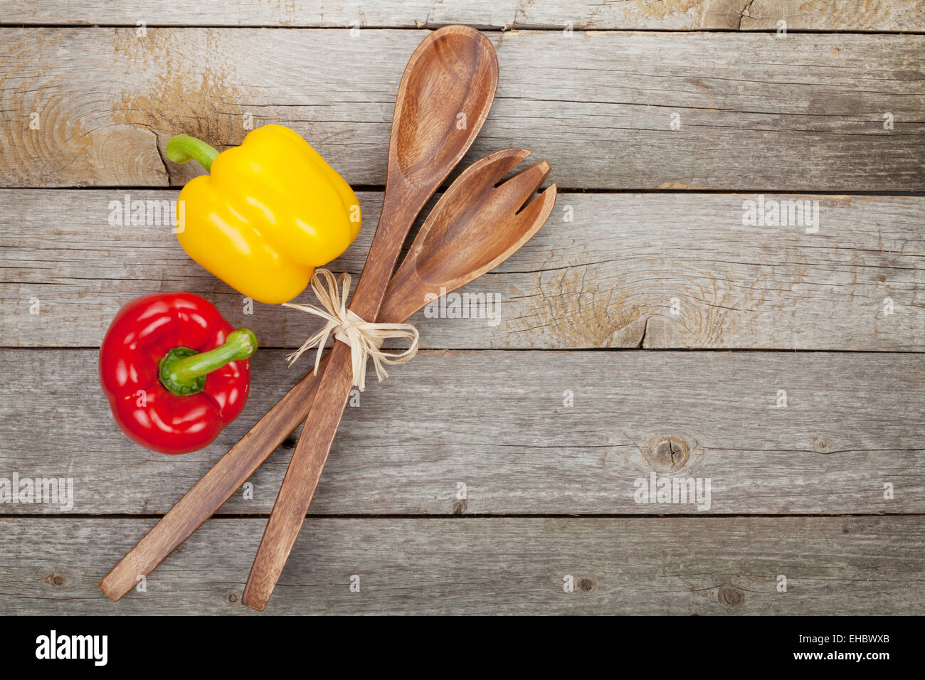Colorful bell peppers and kitchen utensils over wooden table background with copy space - Stock Image