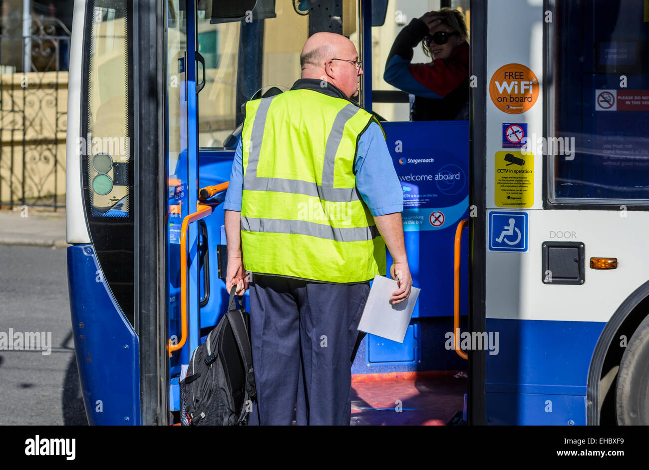 Male bus driver boarding a Stagecoach bus to take over from another driver. - Stock Image