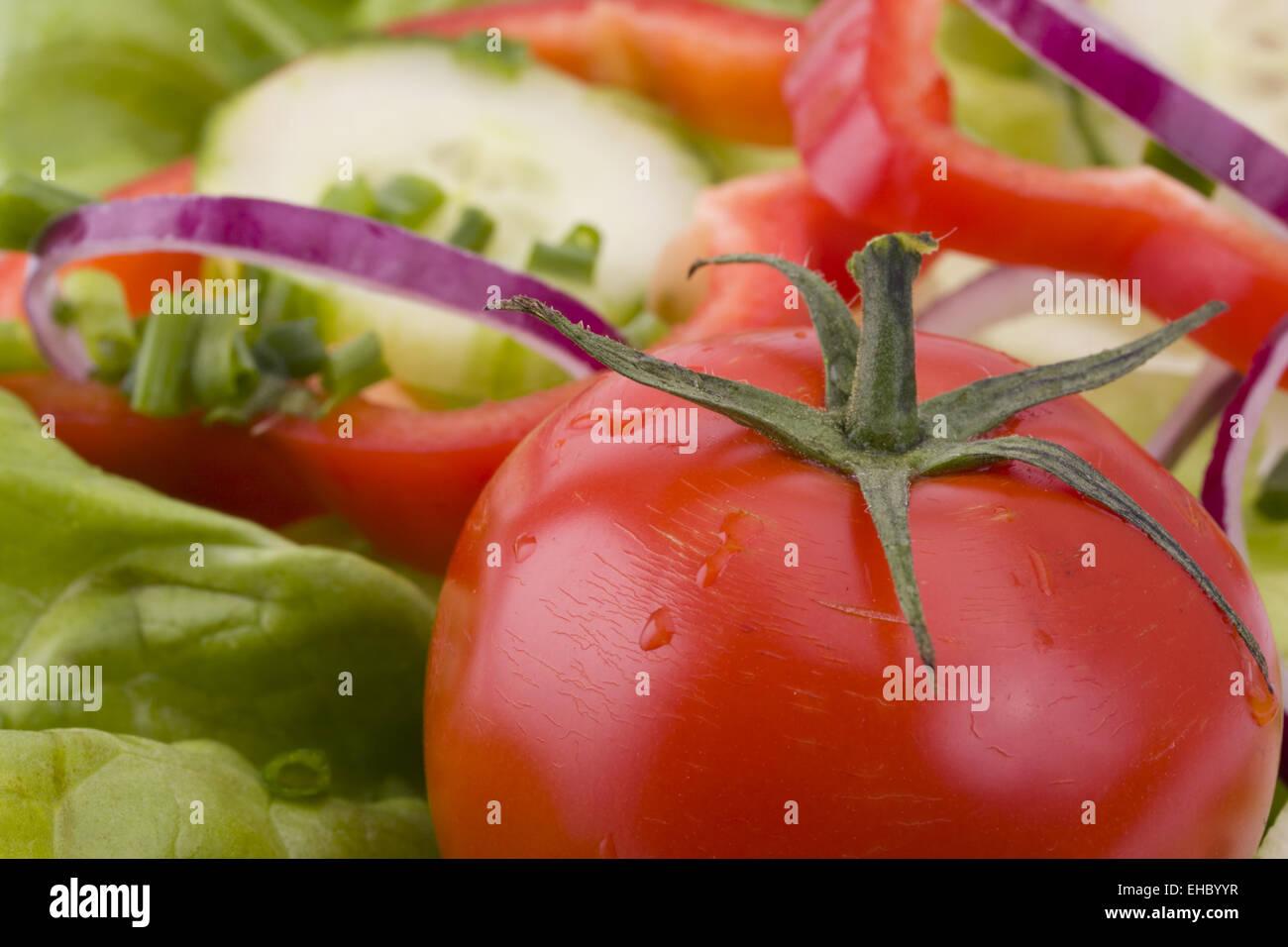 Nahaufnahme einer Tomate auf einem Salatbett - Stock Image