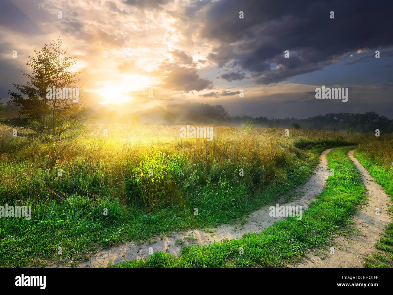 Sun and gray clouds over country road - Stock Image