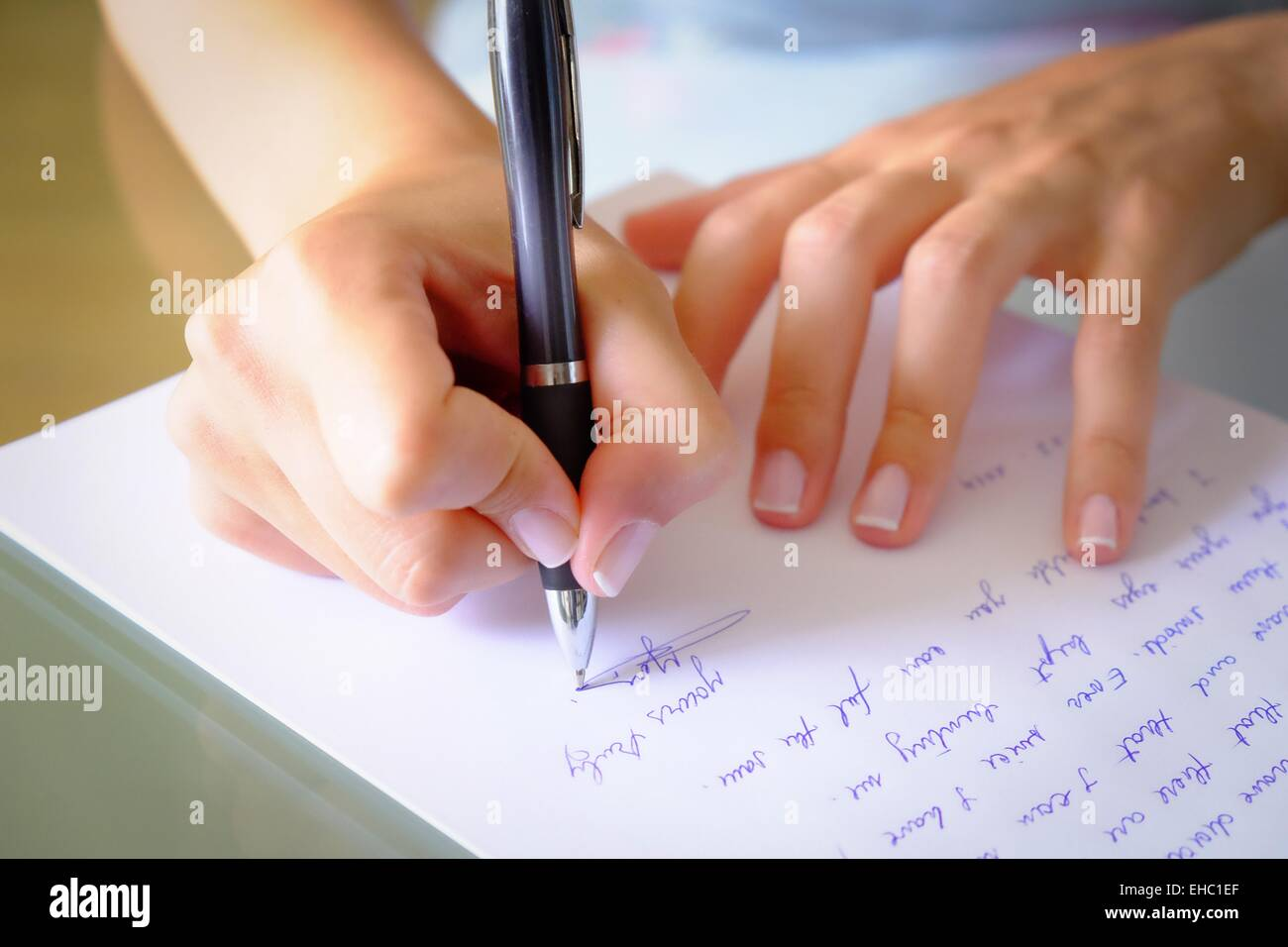 Writing a letter.girl writing a letter with a black pen - Stock Image