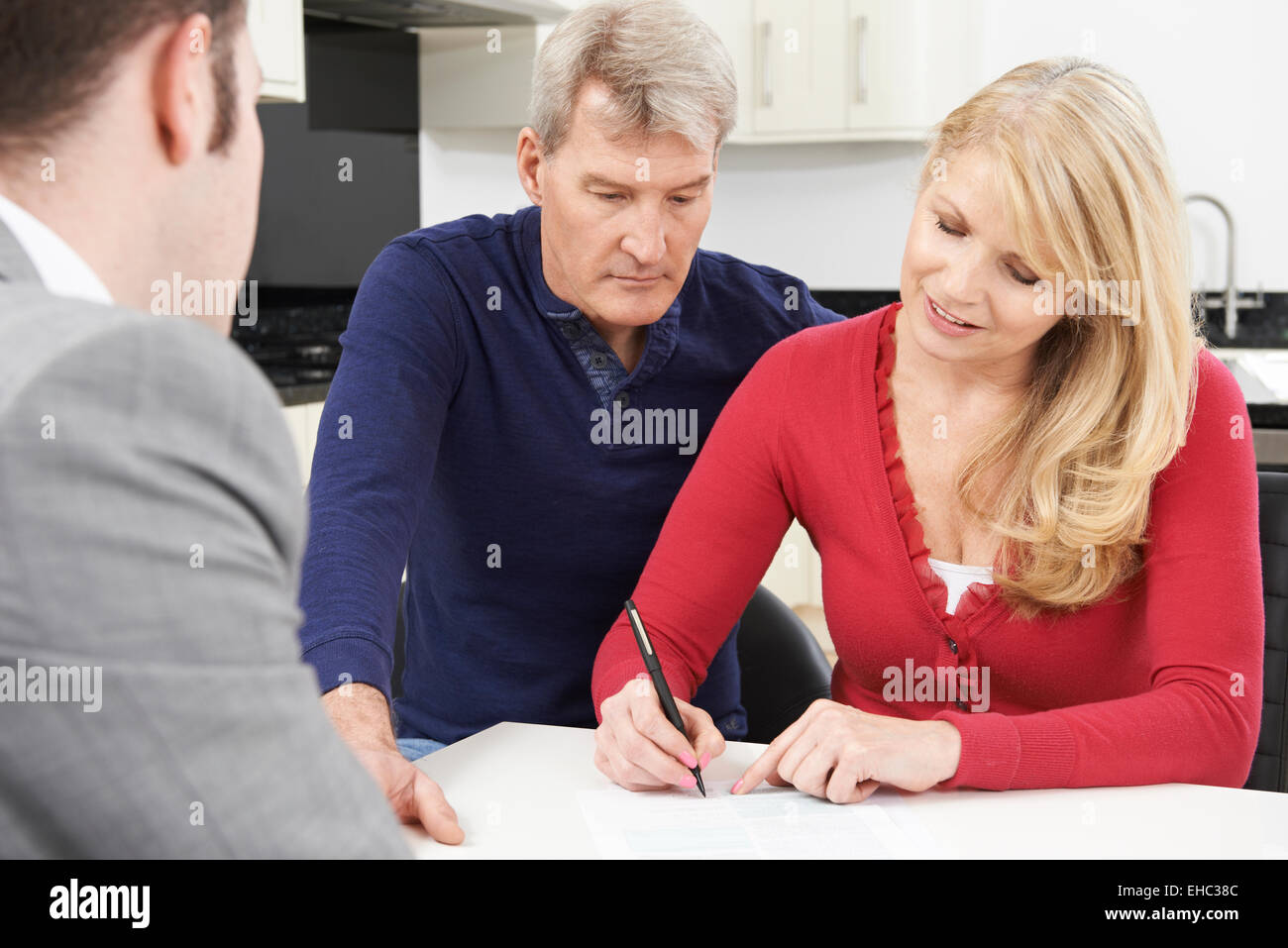 Mature Couple With Financial Advisor Signing Document At Home - Stock Image