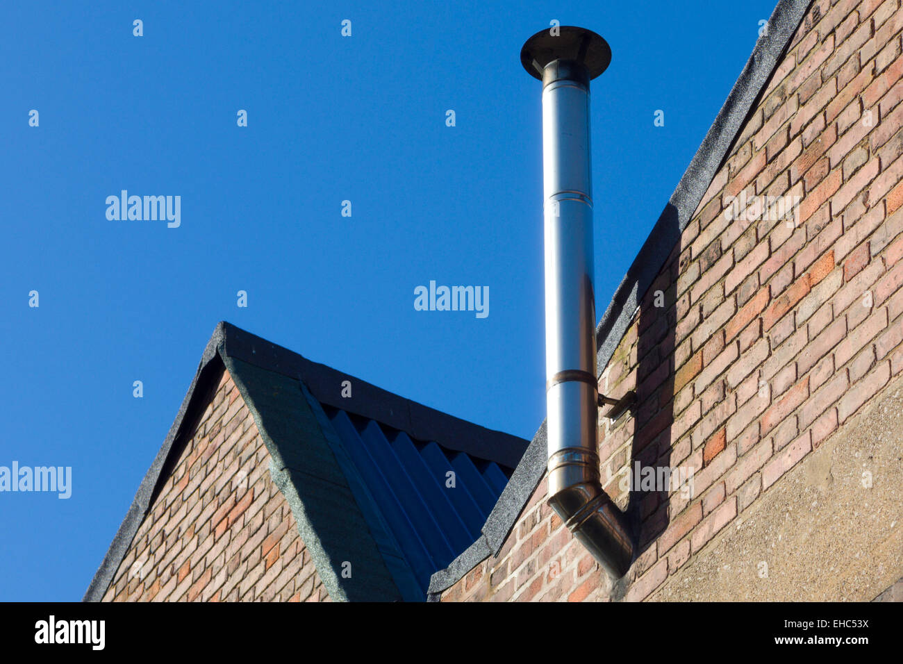 Stainless Steel Industrial Chimney on a Factory Wall, UK Stock Photo