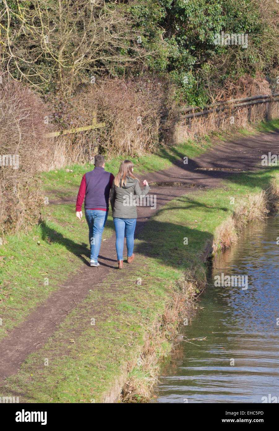 Young Caucasian Couple Waliking Along Stourbridge Canal Towpath, Staffordshire, England, UK in Winter - Stock Image