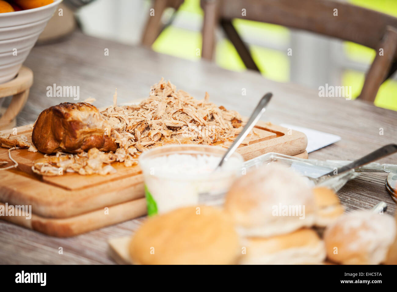 Pulled Pork meat on a chopping board ready for eating - Stock Image