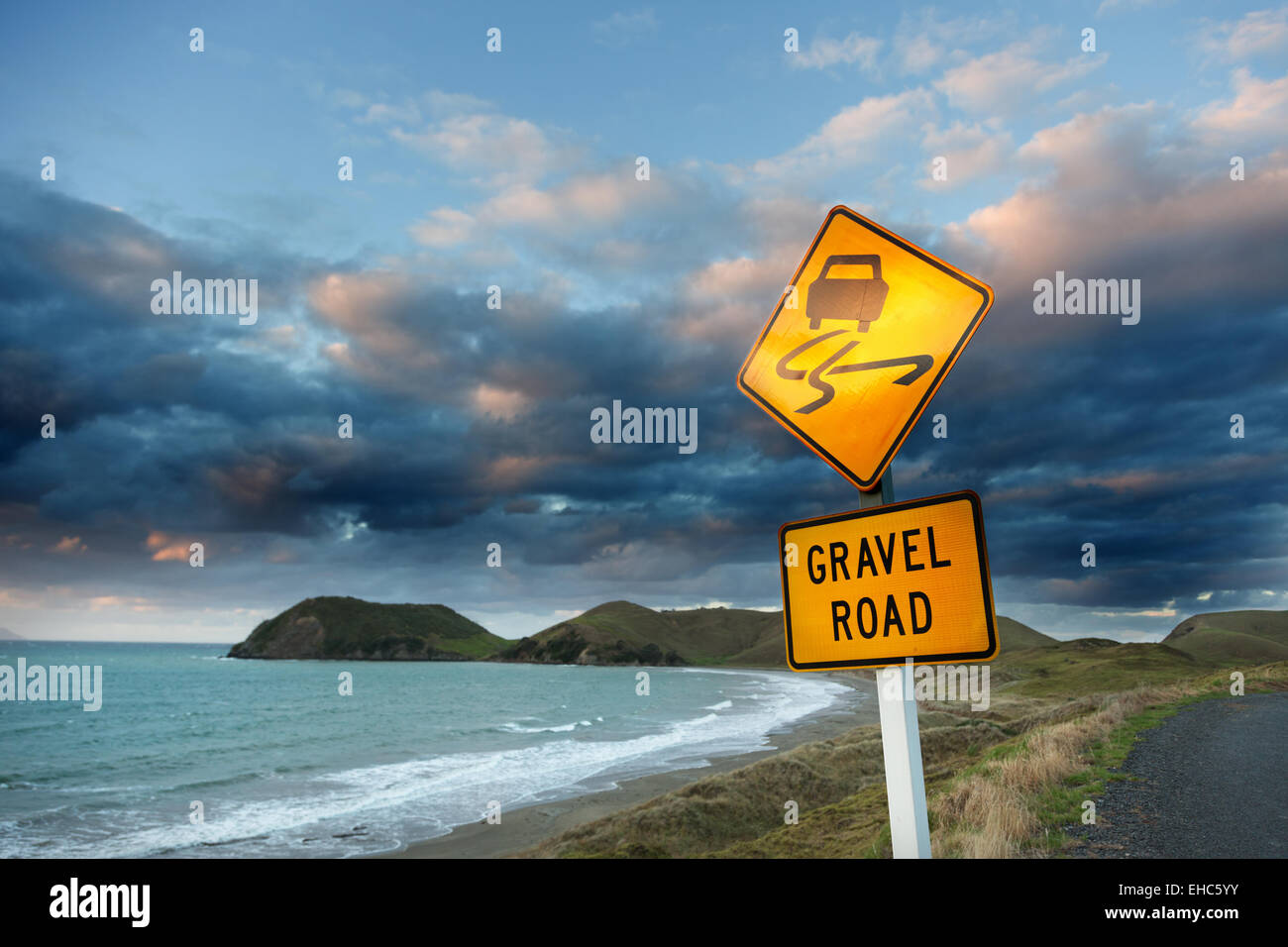 Caution (gravel road) sign on roadside by sea against cloudy sky at dusk. - Stock Image