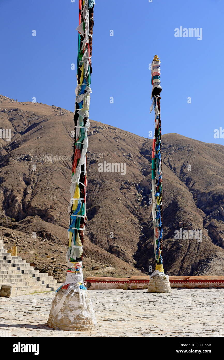 Wooden flagpoles with tied buddhist prayer flags in the square facing the Coqen Hall. Drepung-Rice Heap monastery - Stock Image