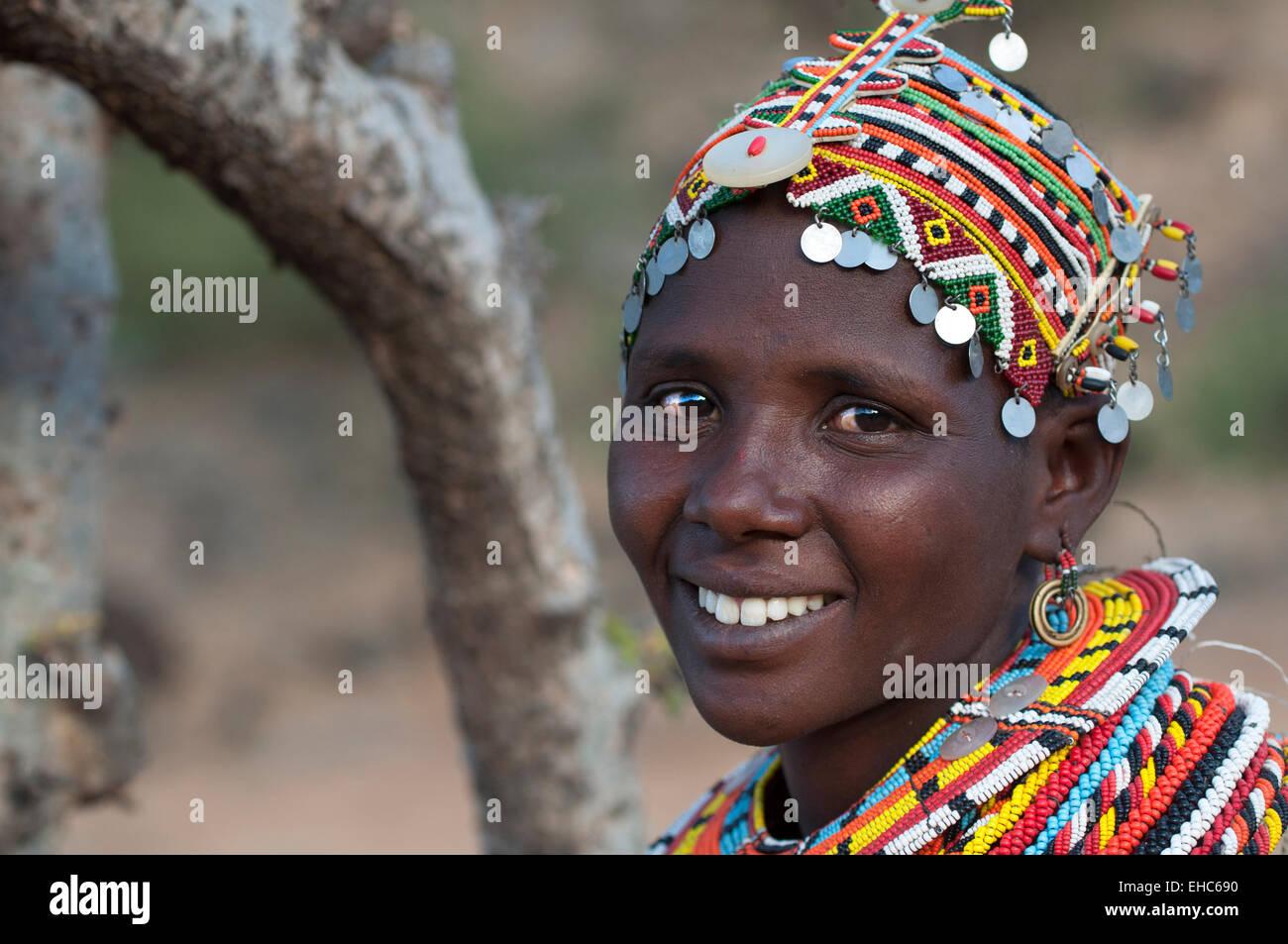 Smiling young Samburu woman with massive colorful necklaces and headdress, Ngurunit area, Kenya - Stock Image